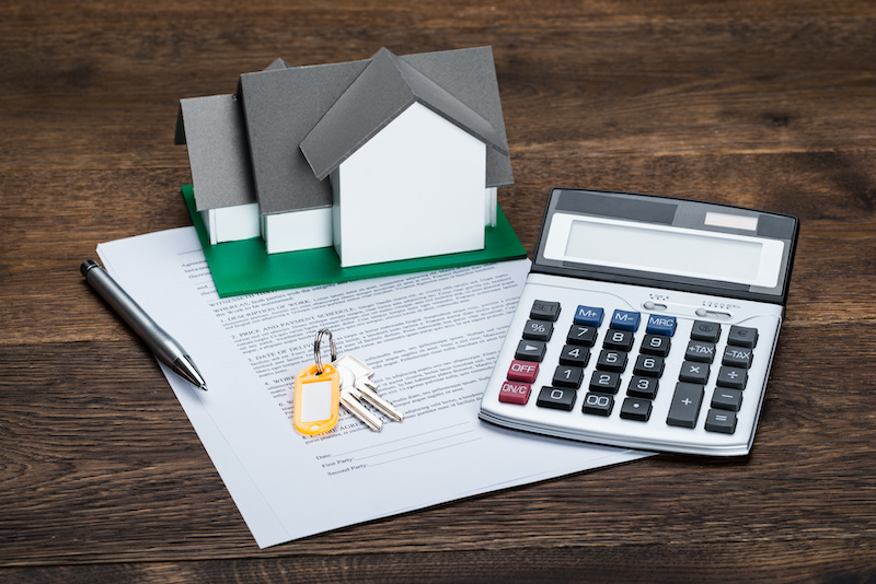 House Model On Contract Paper With Keys And Calculator Kept On Wooden Desk
